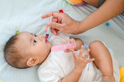 Baby feeding with mineral salt drink, health care concept Stock Photos