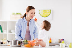 Baby feeding mother with carrot at home kitchen. Family, food, healthy eating, cooking and people concept - little baby feeding his mother with carrot at home Stock Image