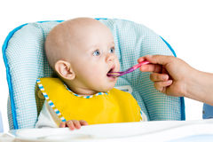 Baby feeding with a spoon Stock Photography