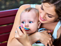 Baby feeding spoon by mother in park outdoor. Weaning . Stock Photos