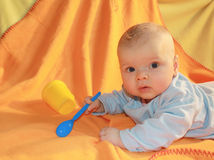 Baby feeding time. Little baby boy on his tummy playing with spoon and cup Royalty Free Stock Photography