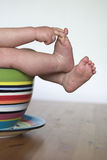 Baby Feet. Image of a baby's legs peeking out over the side of a colorful cup Royalty Free Stock Photo