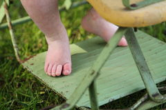 Baby feet closeup outdoors in antique stroller Stock Photos