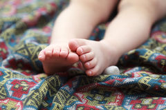 Baby feet on a colorful bedspread with geometric pattern Royalty Free Stock Photography
