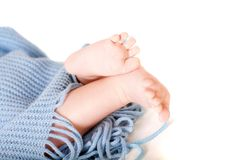 Baby feet covered in blue wrap isolated background Stock Photo