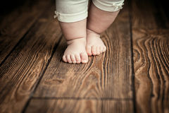 Baby feet doing the first steps. Baby`s first steps. Baby feet . The child is taught to take the first steps Royalty Free Stock Image