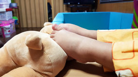 Baby feet with doll close up photo. Baby feet relaxing on bed in the room,close up Royalty Free Stock Photos
