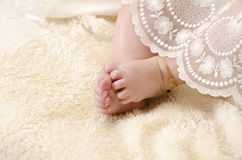 Baby feet. With gold chain, baptism clothes Royalty Free Stock Images