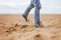 Baby feet in jeans and sneakers running on sand in the summer Royalty Free Stock Photos