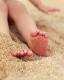 Baby feet lying on yellow beach Royalty Free Stock Image