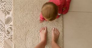 Baby with feet of mom on floor. Top view of unrecognizable baby in red sliders sitting on soft carpet on floor next to crop mother bare legs stock footage
