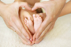 Baby feet in mom's and dad's hands with a blurred background Stock Images