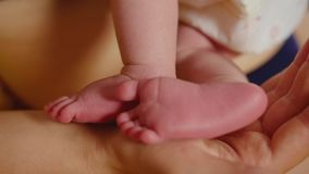 Baby feet in mother hands. Tiny newborn baby's feet on female heart shaped hands closeup. Mom and her child. Happy. Family concept. Beautiful conceptual video stock footage
