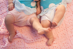 Baby feet in motion. Twins lying on a pink blanket Stock Photos