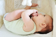 Baby with feet in mouth Royalty Free Stock Image