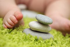 Baby feet next to stack of zen stones Royalty Free Stock Images