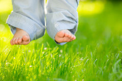 Baby feet over grass. Baby feet over green spring grass Stock Images