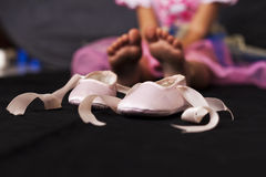 Baby Feet. Pink ballerina baby shoes with baby feet in the background Royalty Free Stock Photos