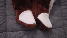 Baby feet in a plush suit. close up stock footage