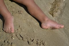 Baby feet in sand. Detail of baby feet on a sandy beach in summer Royalty Free Stock Photo