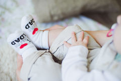 Baby feet in socks with funny inscription Royalty Free Stock Images