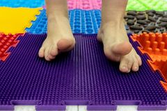 Baby Feet on a Special Orthopedic Carpet. Background. Children`s Feet on the Orthopedic Carpet. Prevention of Flatfoot stock photos