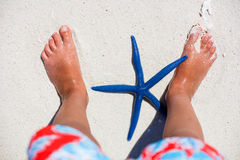 Baby feet with a starfish. Royalty Free Stock Photo