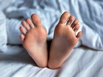 Baby feet under blanket. Baby feet on bed under white blanket Stock Photos