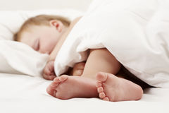Baby feet under white sheet Royalty Free Stock Photo