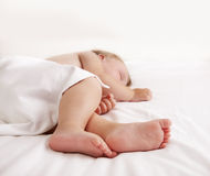 Baby feet under white sheet Stock Photo