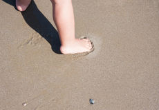Baby feet walking on sand beach Italy Stock Images