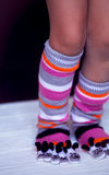 Baby feet in warm, long multicolored socks with toes Royalty Free Stock Image