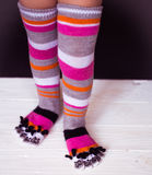 Baby feet in warm, long multicolored socks with toes Royalty Free Stock Photo