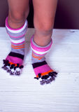 Baby feet in warm, long multicolored socks with toes Stock Photography