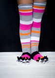 Baby feet in warm, long multicolored socks with toes Stock Photo