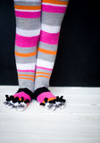 Baby feet in warm, long multicolored socks with toes Royalty Free Stock Photography
