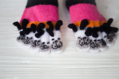Baby feet in warm, long multicolored socks with toes Royalty Free Stock Images