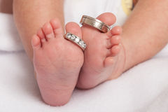 Baby feet with wedding rings parents. Feet of newborn baby with wedding rings parents Stock Photos
