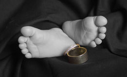 Baby feet with wedding rings selective color. Baby feet with wedding rings black and white selective color Stock Photo