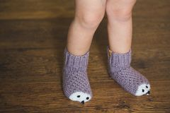 Baby feet in winter hedgehog socks on the wooden floor. Baby feet in winter hedgehog socks on wooden background stock photo