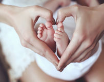 Baby feets in mom hands holding them in heart shape Royalty Free Stock Photos