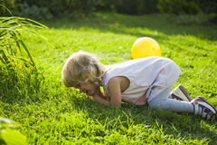 Baby fell and cries on a grass in a garden Stock Image