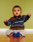 Baby with Finger Food. Adorable 7-month boy sitting on a shiny hardwood floor while holding up his finger food Stock Image