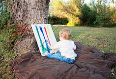 Baby fingerpainting. Baby sitting outside finger painting on canvas Stock Photos