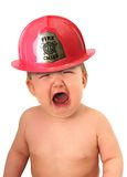 Baby fire fighter. Crying baby wearing a fire fighter hat royalty free stock photos