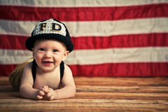 Baby Firefighter. An adorable baby boy dressed as a firefighter on an American flag background royalty free stock image