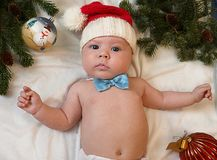 Baby first christmas. Beautiful little baby in Santa hat and bow Stock Photography