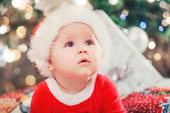 Baby first Christmas. New Year holidays. Baby with santa hat with gift. Living room decorated by Christmas tree and present gift stock image