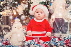 Baby first Christmas. New Year`s holidays. Baby with santa hat with gift. Living room decorated by Christmas tree and present gift stock photography