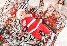 Baby first Christmas. New Year`s holidays. Baby with santa hat with gift. royalty free stock image